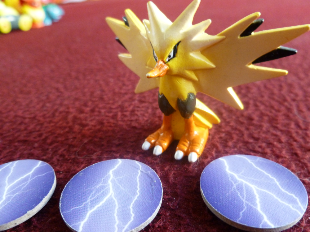 A Zapdos Pokemon figure overlooking lightning tokens